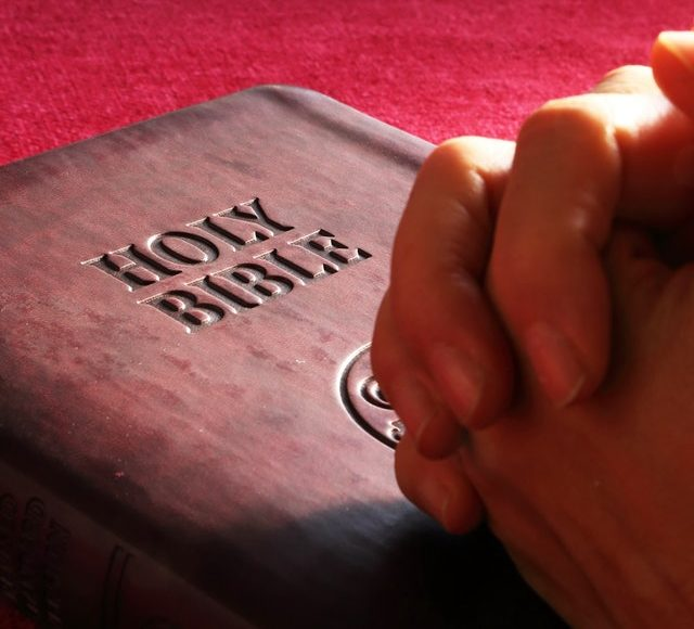 Hands folded on top of Bible.